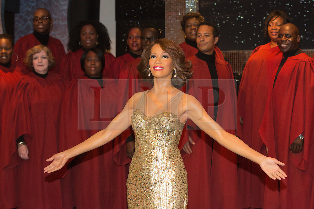 """© Licensed to London News Pictures. 21 October 2013. London, England. The 30-strong """"London Gospel Factory Choir"""" today welcomed the wax figure of singer Whitney Houston at Madame Tussauds London, where it will be on display until the middle of December 2013. Photo credit: Bettina Strenske/LNP"""