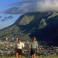 Hikers walk through a park above Cape Town, South Africa. Behind them orographic clouds shroud adjacent Table Mountain.