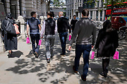 City office workers return to their workplaces carrying identical pink takeaway bags from Sushi retailer, Itsu in the City of London, the capitals financial district, on 27th May 2021, in London, England.