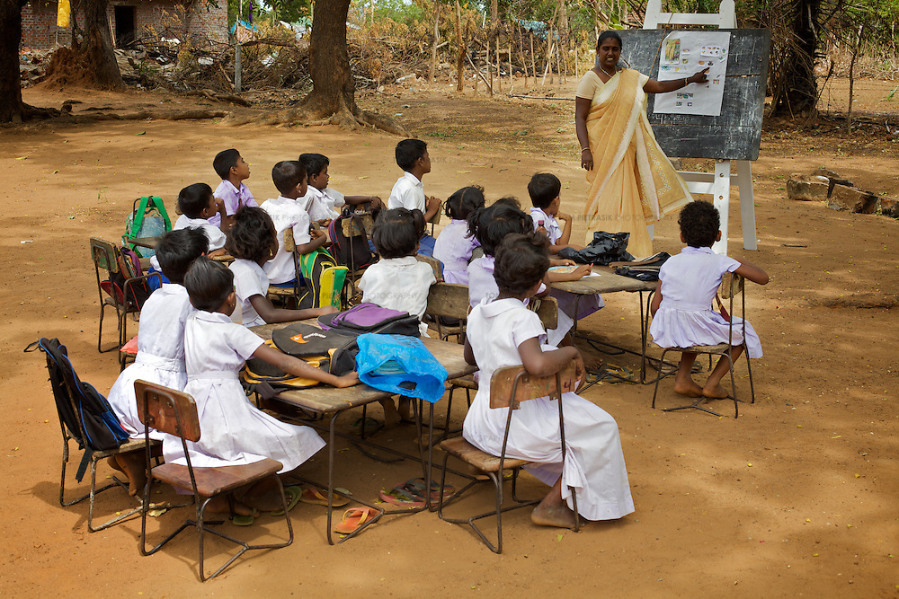 A teacher conducts an outdoor class in the grounds of the Thikilivattai Government Tamil Mixed School in Batticaloa District. <br /> <br /> Thikilivattai Government Tamil Mixed School reopened in May 2008 after local conflict between the LTTE and SLA  troops eased. There are now 351 students in grades 1-9 with a teaching staff of 18. The school has no water supply. Though many of the pupils' parents are not well educated themselves (most are employed in casual paddy cultivation, fishing and seasonal day-wage labour), there is a parents' mobilisation committee that encourages pupil attendance and is involved in helping keep the school clean. The school has an active sports department. Many of the students suffer with the trauma and stress associated with those living in conflict situations. The staff must deal with these issues as well as the personal difficulties that they themselves suffer living in a conflict environment. UNICEF have provided three temporary learning spaces to make up for the lack of space in the original school building. A further two classes must be accommodated beneath trees. UNICEF have also supplied the school furniture.<br /> <br /> Photo: Tom Pietrasik<br /> Batticaloa District, Sri Lanka<br /> September 30th 2009