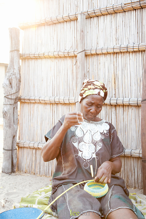 A woman weaving baskings using old plastic bags; one of the local initiatives in the village of Seronga in the Okavango Delta, Botswana