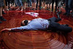 London, UK. 27th August, 2021. An environmental activist from Extinction Rebellion dressed as a financier covers himself in fake blood in Paternoster Square following a Blood Money March through the City of London on the fifth day of Impossible Rebellion protests. Extinction Rebellion were intending to highlight financial institutions funding fossil fuel projects, especially in the Global South, as well as law firms and institutions which facilitate them, whilst calling on the UK government to cease all new fossil fuel investment with immediate effect.