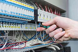 Close-up of electrician installing cable in distribution fusebox, Munich, Bavaria, Germany