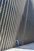 Beneath new architecture, a City worker carrying a dustpan and brush walks along Bevis Marks in the City of London, the capitals financial district, on 17th June 2019, in London, England.