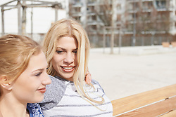 Two friends sitting on a bench in a playground, Munich, Bavaria, Germany