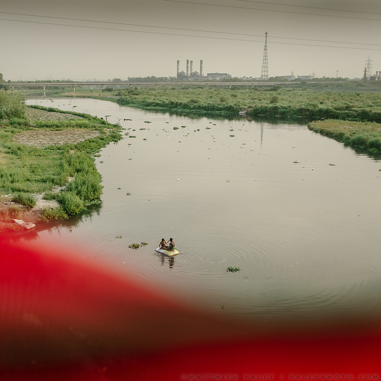 A prayer flag on the bottom. Hindu come to offer prayers at the polluted Yamuna river next to ITO bridge.