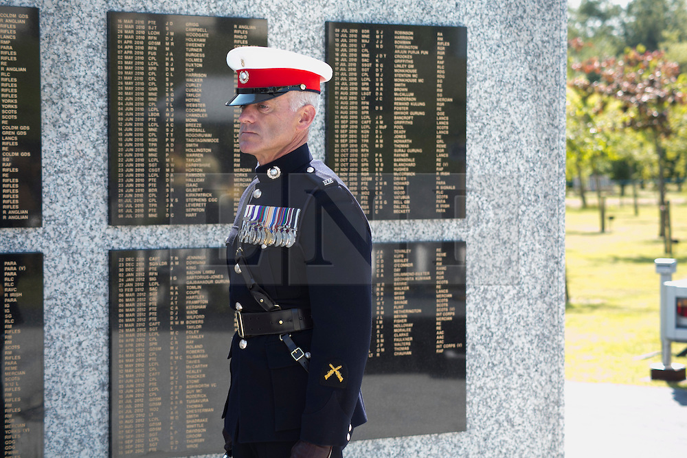 © Licensed to London News Pictures. 11/06/2015. National Memorial Arboretum, Alrewas, Staffordshire, UK. The service to mark the Rededication of the Bastion Memorial. The memorial was begun in Helmand Province in 2006, deconstructed in 2014 and now replicated at the National Memorial Arboretum in Staffordshire. Around two thousand people took part in the service including HRH Prince Harry, the Prime Minister David Cameron and senior members of the Armed Forces. Pictured, Warrant Officer Class 1 MATTHEW TOMLINSON 3 Commando in front of the wall. Photo credit : Dave Warren/LNP