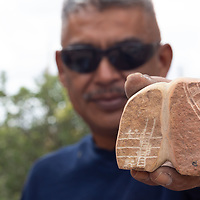 Daryl Shock Sr., 45, shows some of the details he has added to his newest fetish carving, during the Zuni Art Walk and Market on Saturday in Zuni Pueblo.