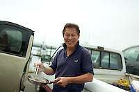Richard Lang cooks up tuna that he just bought fresh off a boat at the Newport Bay Dock, Oregon.