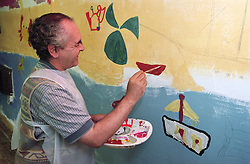 Man with learning disability painting wall mural in community centre,