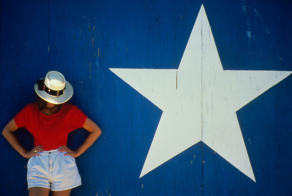 woman standing in front of a wall painted as the Texas flag