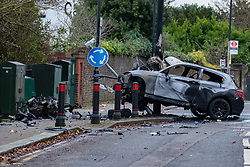 © Licensed to London News Pictures. 07/12/2019. London, UK. The scene of a fatal road traffic collision where a black BMW hit a lamp post, the impact ripped the engine block from the car and it caught fire.<br /> Police were called at 09:08 GMT on Saturday 7th December 2019 to reports of a car in collision with a lamp post on Dollis Hill Lane at the junction with Brook Road, NW2. Metropolitan Police Officers, the London Ambulance Service and London Fire Brigade attended. Two people were recovered from the vehicle. The male driver was pronounced dead at the scene at 09:21 GMT. The passenger has been taken to a central London hospital. Photo credit: Peter Manning/LNP