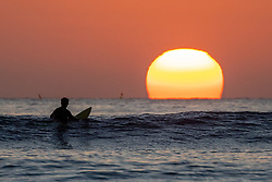 © Licensed to London News Pictures. 14/04/2020. Padstow, UK. A surfer waits for waves as the sun sets over Constantine Bay on the north coast of Cornwall this evening. The weather in Cornwall is forecast to be warm until the weekend. Photo credit : Tom Nicholson/LNP