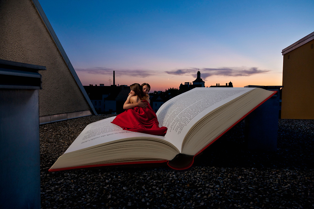 young couple sitting in a hughe book lying on the top of a roof at night