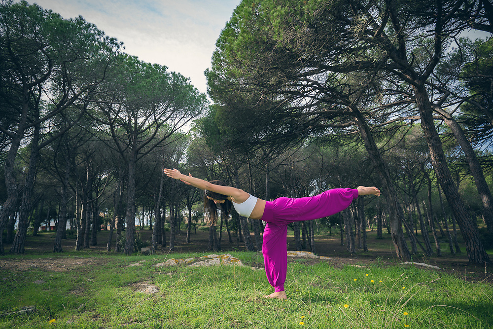Young woman doing yoga outdoors Warrior 3 pose