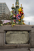 A floral memorial on the southern end of Westminster Bridge of the Houses of Parliament while Londoners gather on Westminster Bridge, the scene of the Terrorist attack 7 days ago in which 4 people died and others severely injured, on 29th March 2017, London, England. Hundreds crossed the Thames in a silent vigil to commemorate the four and at 2.40pm when Khalid Masood drove into crowds on the bridge before stabbing a police officer at the nearby Palace of Westminster, the crowds fell silent, many bowing their heads.