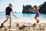 Children jumping, playing and building sand castles at Beauport Beach on a sunny summer day in Jersey, Channel Islands