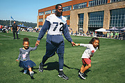 Michael Bennett walks across the field with his daughters Ollie, left, and Blake, right, after a Seahawks pre-season practice, Tuesday, Aug. 16, 2016 at Virginia Mason Athletic Center. (Genna Martin, seattlepi.com)