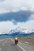 Cyclist biking toward El Chalten and the impressive FizRoy mountain massif, Argentina