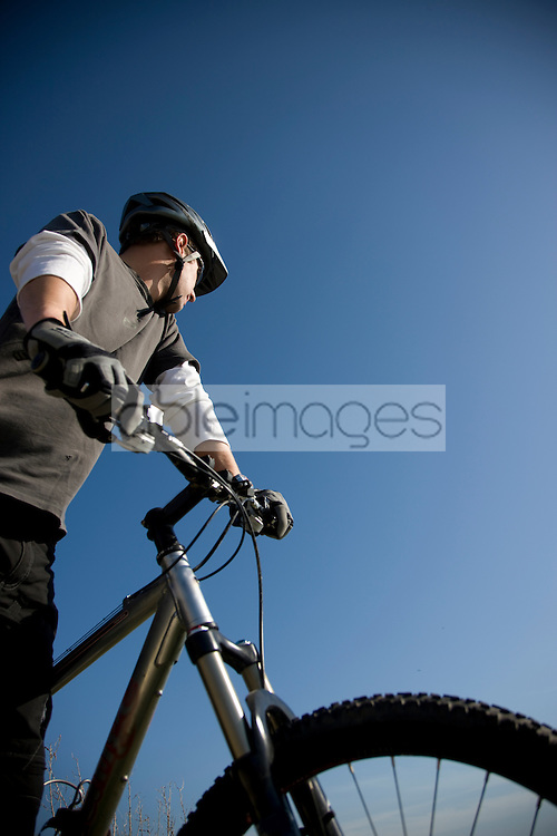 Man on a bycicle against blue sky