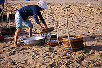Person sorting fish on China Beach, Vietnam.