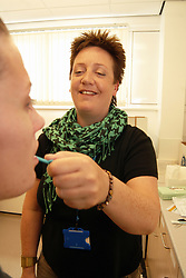 Drug addiction worker swabs a client's tongue to check for infection UK