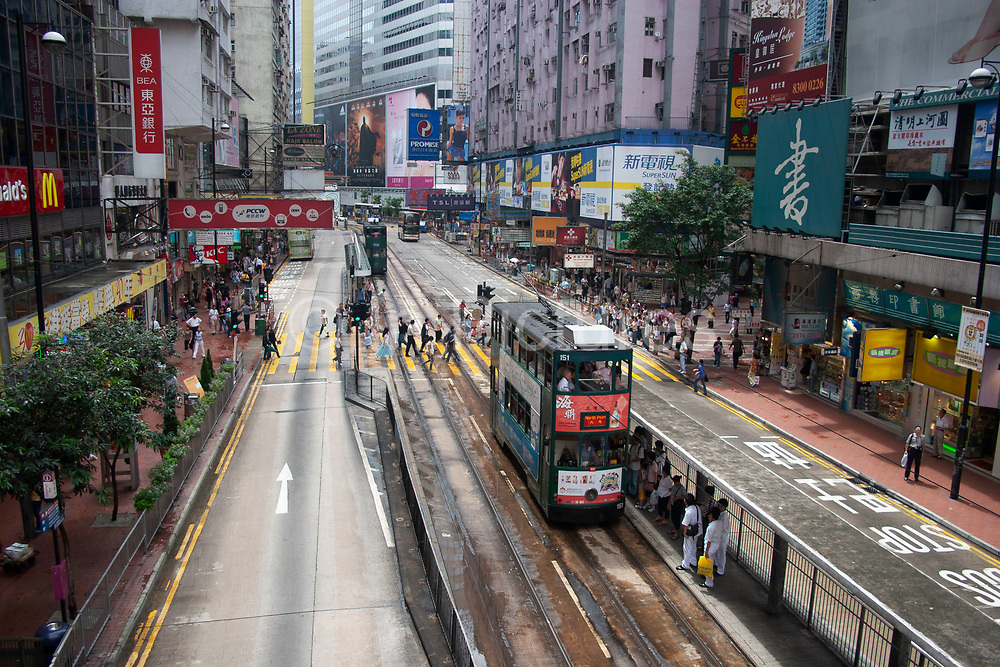 Buses and a trams in Causeway Bay, Hong Kong, China. Transportation around Hong Kong can have a decisively colonial feel, harping back to Hong Kongs pre-handover era under British rule. Double-decker buses and trams provide a cheap and easy way of moving around the busy city above ground.