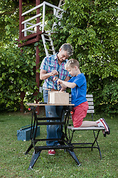 Building birdhouse father son together working