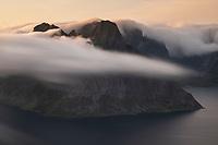 Summer sea fog flows over Olstind mountain peak viewed from Reinebringen, Reine, Moskenesøy, Lofoten Islands, Norway