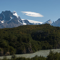 The Grey River flows through  a southern beech forest below the Grand Tower of Paine and Horns of Paine in Torres del Paine National Park, Chile.