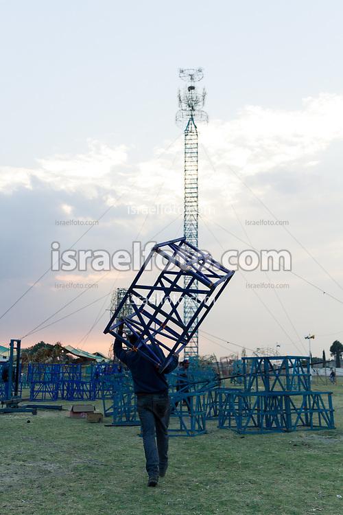 Un hombre acarrea estructura para armar el castillo con el que concursará en la Feria Nacional de la Pirotecnia de Tultepec.