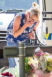 © Licensed to London News Pictures. 28/05/2018. Stockport, UK. A woman reads tributes and looks at flowers left at the scene outside The Salisbury Club on Truro Avenue in the Brinnington area of Stockport, Greater Manchester, where a car collided with pedestrians late last night, killing one man and injuring others.  A murder investigation has been launched. Police later recovered a black Audi A4 which fled the scene. Photo credit: Joel Goodman/LNP