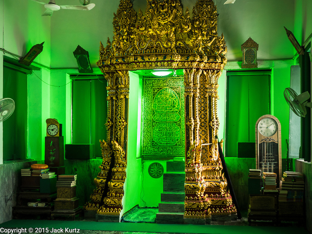 """15 JULY 2015 - THONBURI, BANGKOK, THAILAND:  The """"mihrab,"""" a niche which indicates the direction of Mecca, in Bang Luang Masjid (Masjid is the Thai word for mosque.) Located on the west bank of the Chao Phraya River and built in the reign of King Rama I (1782-1809), Bangluang Mosque is one of the oldest mosques in Bangkok and is unique because it's designed in a traditional Thai style and decorated with Thai, European, and Chinese art. The Mosque carries Islamic symbolic features such as 30 pillars, 12 windows and 1 door which represent the numbers of chapters in the Koran and the 13 regulations of Islamic worshipping ritual.    PHOTO BY JACK KURTZ"""