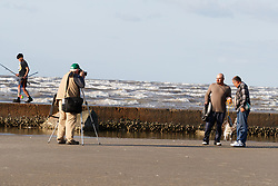 Photographer taking pictures of fishermen and their catch along jetty, East Beach, Galveston Bay, Galveston, Texas, USA