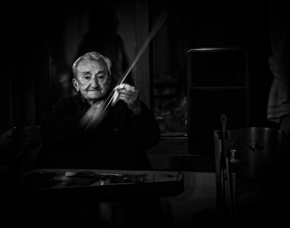 Violin player cleaning the bow before the performance. Dark black and white
