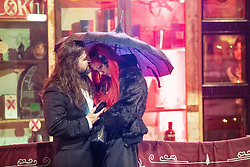 """© Licensed to London News Pictures . 21/12/2018 . Manchester , UK . A man and a woman huddle under an umbrella in rain . Revellers out in Manchester City Centre overnight during """" Mad Friday """" , named for historically being one of the busiest nights of the year for the emergency services in the UK . Photo credit : Joel Goodman/LNP"""
