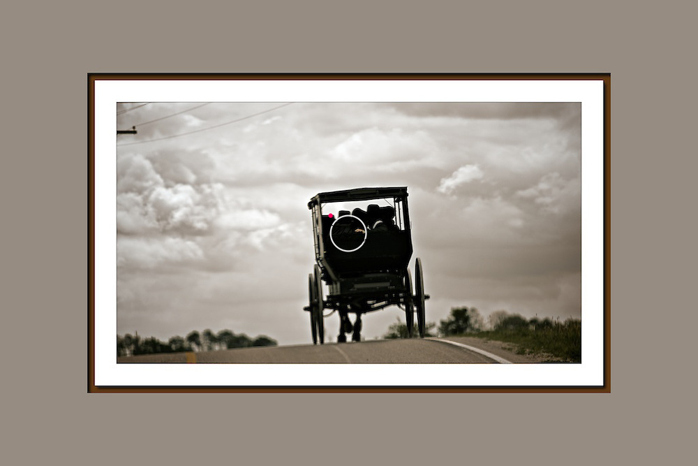An Amish horse and buggy trots down a country road between Orleans and Livonia in Indiana. It appears to be an Amish courtship with a young man and woman in the back seat, while four ladies are all seated up front. Look closely and you can see the young man's hand on the young woman's shoulder.