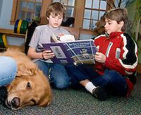 How Much is that Doggy in the Window?  Holly Raus' golden retriever Benson doesn't looked concerned in the least by the book choice read by Nik Boutwell and Seth Valpey during the Tales for Tails program at Gilford Public Library.  The Tales for Tails program runs every Thursday afternoon 3:15 to 4:00 pm in the childrens reading room from now through June.  (Karen Bobotas/for the Laconia Daily Sun)
