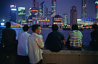 View from the Bund in the evening,  locals view the modern architecture of the Pudong skyline, Shanghai's financial district.