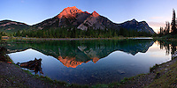 I waited a long time after sunrise to make this panoramic image of Mount Lorette reflected in the Lorette Ponds.  I really wanted to catch the alpenglow on the peak but it didn't happen initially and the morning glow faded as the sun came over the horizon.  It wasn't until the sun rose above the mountain peaks to the east of my position that the Alpenglow began.  Fortunately I made a series of images quickly because it was only a minute or so after this that  a flock of ducks flew in and landed on the pond in front of me, detroying the glassy finish on the surface.  The alpenglow was over before the pond was calm again.  But I got the image I wanted!!...©2009, Sean Phillips.http://www.Sean-Phillips.com