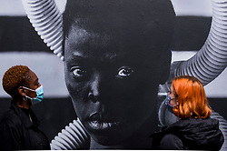 """© Licensed to London News Pictures. 03/11/2020. LONDON, UK. Staff members view a self-portrait """"Sebenzile, Parktown"""", 2016, by Zanele Muholi. Preview of the first major UK exhibition by South African visual activist Zanele Muholi at Tate Modern.  260 photographs document black lesbian, gay, trans, queer and intersex lives in South Africa.  The show runs 5 November to 7 March 2021, but will be interrupted by England's coronavirus pandemic lockdown currently due to last 5 November to 2 December.   Photo credit: Stephen Chung/LNP"""