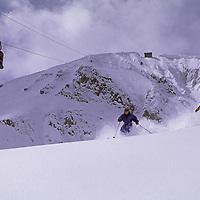 SKIING, Big Sky, Montana. Patrick Shanahan & Maclaren Johnson ski new powder on Cue Ball, underneath Lone Peak Tram.