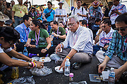 """15 JANUARY 2014 - BANGKOK, THAILAND: SUTHEP THAUGSUBAN, former Deputy Prime Minister of Thailand and leader of the Shutdown Bangkok anti-government protests, eats his lunch in the Ekkamai intersection in Bangkok. The protest march stopped at Ekkamai for a picnic. Tens of thousands of Thai anti-government protestors continued to block the streets of Bangkok Wednesday to shut down the Thai capitol. The protest, """"Shutdown Bangkok,"""" is expected to last at least a week. Shutdown Bangkok is organized by People's Democratic Reform Committee (PRDC). It's a continuation of protests that started in early November. There have been shootings almost every night at different protests sites around Bangkok. The malls in Bangkok are still open but many other businesses are closed and mass transit is swamped with both protestors and people who had to use mass transit because the roads were blocked.    PHOTO BY JACK KURTZ"""