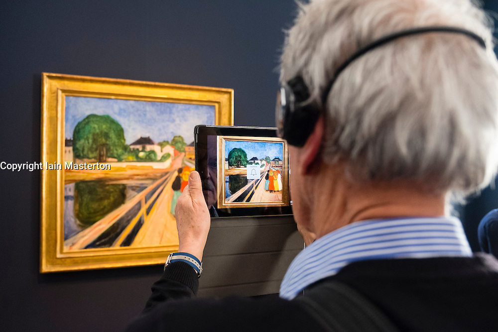 Visitor photographing painting The Girls on the Bridge, by Edvard Munch with tablet camera at new Museum Barberini in Potsdam Germany
