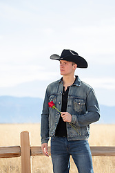 cowboy holding a red rose on a ranch