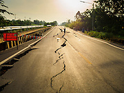 14 JULY 2015 - THAILAND:  A man photographs a damaged road in Pathum Thani province. The road bed collapsed because of subsidence. The drought that has crippled agriculture in central Thailand is now impacting residential areas near Bangkok. The Thai government is reporting that more than 250,000 homes in the provinces surrounding Bangkok have had their domestic water cut because the canals that supply water to local treatment plants were too low to feed the plants. Local government agencies and the Thai army are trucking water to impacted communities and homes. Roads in the area have started collapsing because of subsidence caused by the retreating waters. Central Thailand is contending with drought. By one estimate, about 80 percent of Thailand's agricultural land is in drought like conditions and farmers have been told to stop planting new acreage of rice, the area's principal cash crop.      PHOTO BY JACK KURTZ