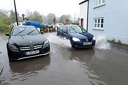 © Licensed to London News Pictures. 26/10/2019. Crickhowell, Powys, Wales, UK. Motorists drive through flood water in Bridge Street in Crickhowell, Powys. Rain falls relentlessly and the level of the river Usk rises dramatically. Water enters The Bridge End Inn basement in Bridge Street, Crickhowell  in Powys. Photo credit: Graham M. Lawrence/LNP