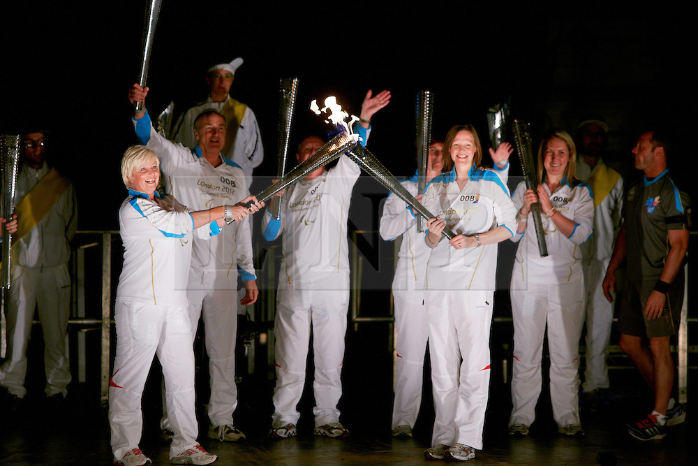 © Licensed to London News Pictures.  28/08/2012. AYLESBURY, UK. Paralympic torch bearers transfer the flame, known as a kiss, during a Paralympic flame celebration in Aylesbury town centre. Nearby Stoke Mandeville is the birthplace of the Paralympics and a 24 hour torch relay began at 8pm this evening (Tuesday) and will finish in the Olympic Park in Stratford tomorrow. Photo credit :  Cliff Hide/LNP