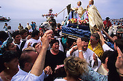 """Europe, France, Camargue, Saintes Maries de la Mer. Gitan Gypsies carry the two Saint Marys in their boat to the seashore. The Gypsy festival """"le Pelerinage des Gitans aux Saintes Maries de la Mer"""" takes place every year in mid May. Gypsies arrive from all over Europe a few weeks before the main festival days, the 24th and 25th May.  The pilgrimmage is Catholic but many Gypsies, Manouche, Gitans, Roma come to see their patron 'Saint Sara' and for the festival atmosphere, the yearly gathering of friends, the music and dance. Gypsies are still regarded with much distrust and racism, they are not liked by the shopkeepers but are well treated by the gentry, especially the Baroncelli family who were instrumental in making this officially a Gypsy festival. One Hundred years ago the Gypsies were not allowed into the church, as it is they still have to camp outside the town."""