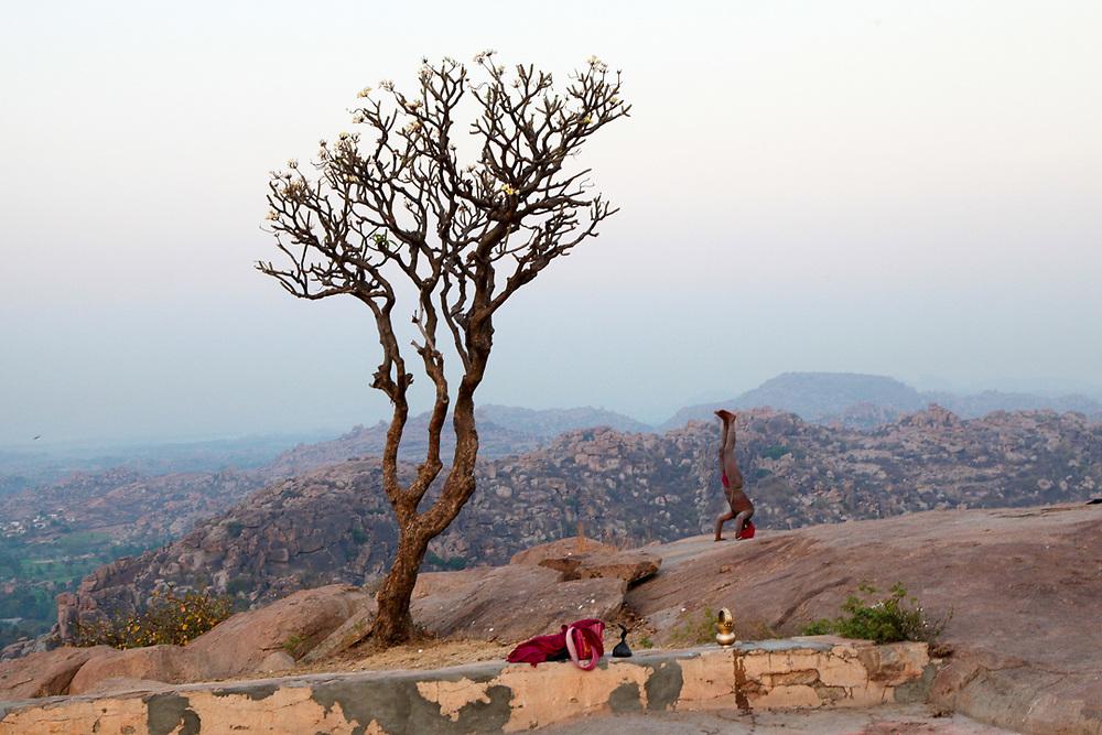 An Indian Sannyasi is praticing Yoga before sunrise on top of Anjanadri Hill near Hampi, India. <br /> Photo by Lorenz Berna